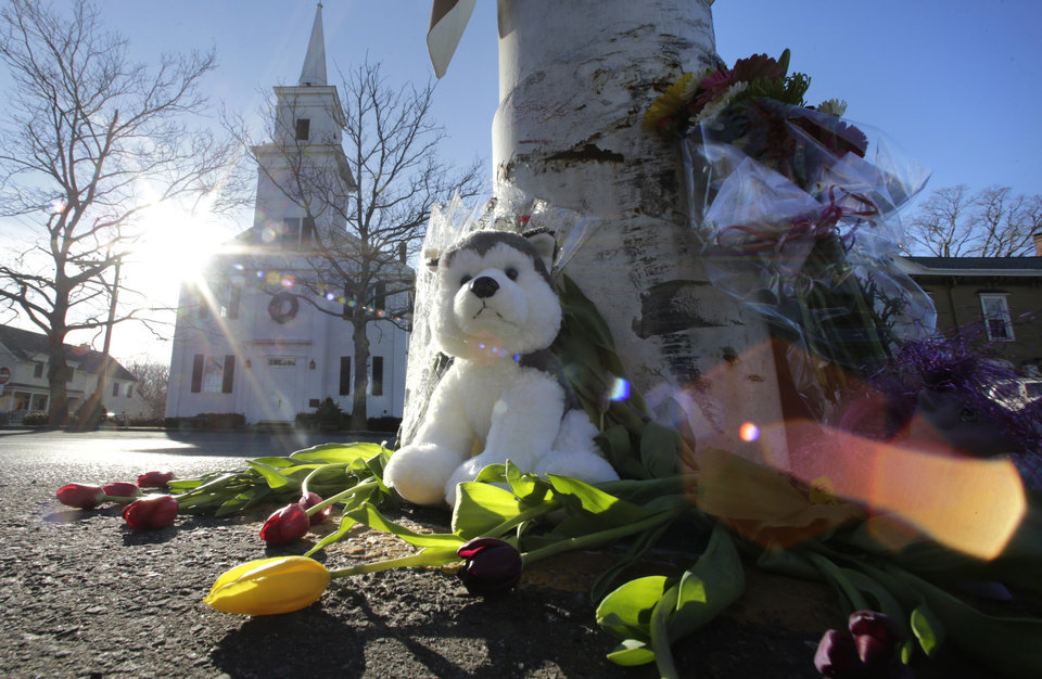 Photo - Flowers and stuffed animals of a makeshift memorial for school shooting victims encircle the flagpole at the town center in Newtown, Conn., Saturday, Dec. 15, 2012.  The massacre of 26 children and adults at Sandy Hook Elementary school elicited horror and soul-searching around the world even as it raised more basic questions about why the gunman, 20-year-old Adam Lanza, would have been driven to such a crime and how he chose his victims. (AP Photo/Charles Krupa) ORG XMIT: CTCK106