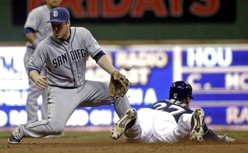 Photo - San Diego Padres second baseman Jedd Gyorko can't handle the throw as Milwaukee Brewers' Carlos Gomez steals second during the third inning of a baseball game Tuesday, April 22, 2014, in Milwaukee. (AP Photo/Morry Gash)