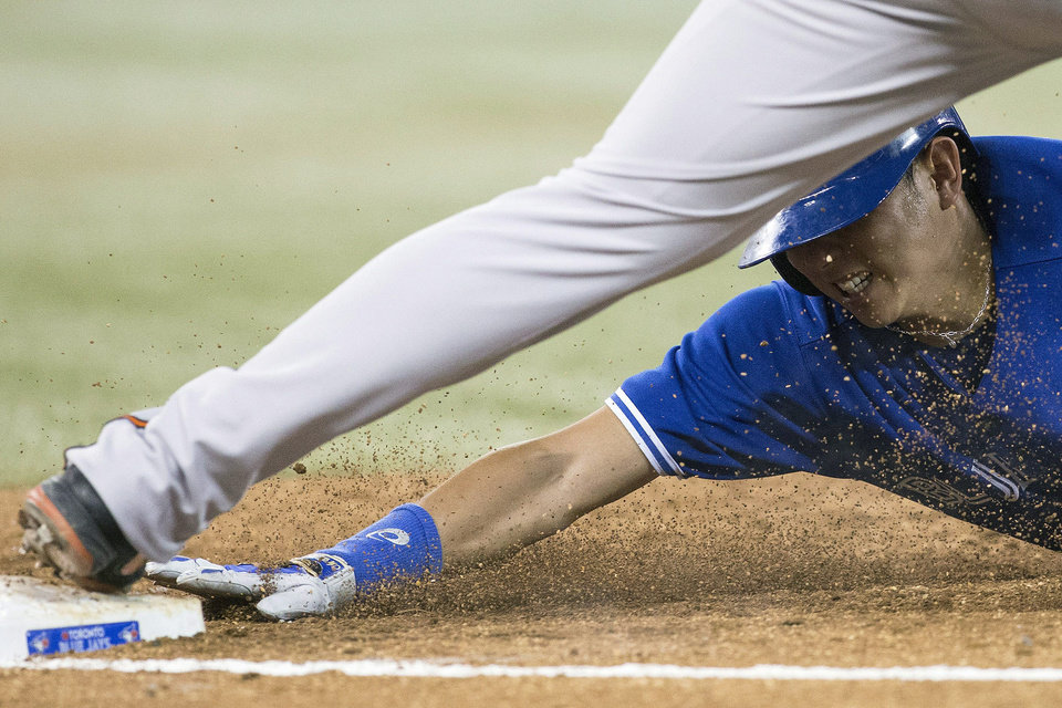 Photo - Toronto Blue Jays' Munenori Kawasaki, bottom, is forced out at first on a double play by Baltimore Orioles' Travis Ishikawa during the fifth inning of a baseball game in Toronto, Saturday June 22, 2013. (AP Photo/the Canadian Press, Chris Young)