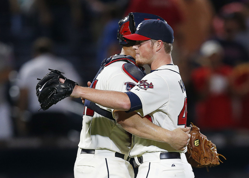 Photo - Atlanta Braves closer Craig Kimbrel, right, and catcher Evan Gattis, left, celebrate their 2-0 victory over Chicago Cubs in a baseball game Saturday, May 10, 2014, in Atlanta.  (AP Photo/John Bazemore)