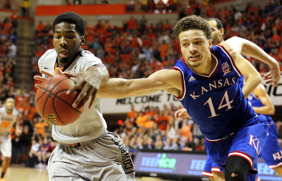 Photo - OSU's Tavarius Shine (5) and Kansas' Brannen Greene (14) fight for a loose ball during the men's college basketball game between Oklahoma State University and the University of Kansas at Gallagher-Iba Arena in Stillwater, Okla.,  Saturday, Feb. 7, 2015. OSU won 67-62. Photo by Sarah Phipps, The Oklahoman