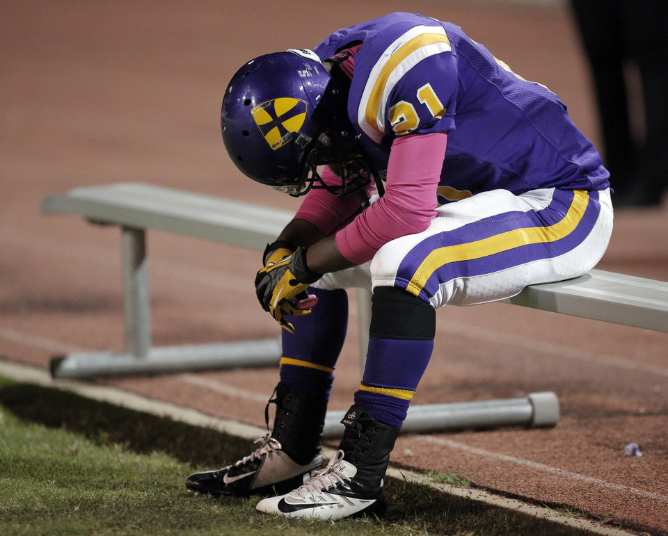 Photo - NWC's Lorenzo Alexander (21) rests on the bench during a high school football game between Northwest Classen and El Reno at Taft Stadium in Oklahoma City, Friday, Oct. 5, 2012.  Photo by Garett Fisbeck, The Oklahoman