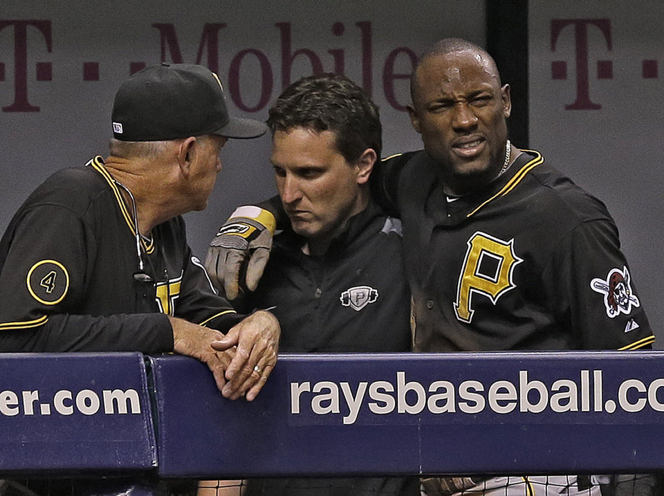 Photo - Pittsburgh Pirates' Starling Marte, right, is helped to the clubhouse after getting injured attempting to steal second base during the fifth inning of an interleague baseball game against the Tampa Bay Rays, Tuesday, June 24, 2014, in St. Petersburg, Fla. (AP Photo/Chris O'Meara)