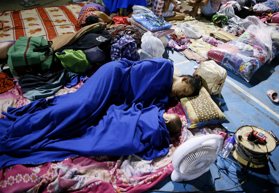 Photo - Typhoon evacuees sleep as they are housed at a school gymnasium after fleeing their homes due to flooding brought by Typhoon Koppu in Cabanatuan city in northern Philippines Monday, Oct. 19, 2015. The slow-moving typhoon blew ashore with fierce wind in the northeastern Philippines early Sunday, toppling trees and knocking out power and communications and forcing the evacuation of thousands of villagers. Koppu weakened once on land, and by Monday afternoon, Koppu had weakened into a tropical storm over Ilocos Norte province with winds of 105 kilometers (65 miles) per hour and gusts of up to 135 kph (84 mph). (AP Photo/Bullit Marquez)
