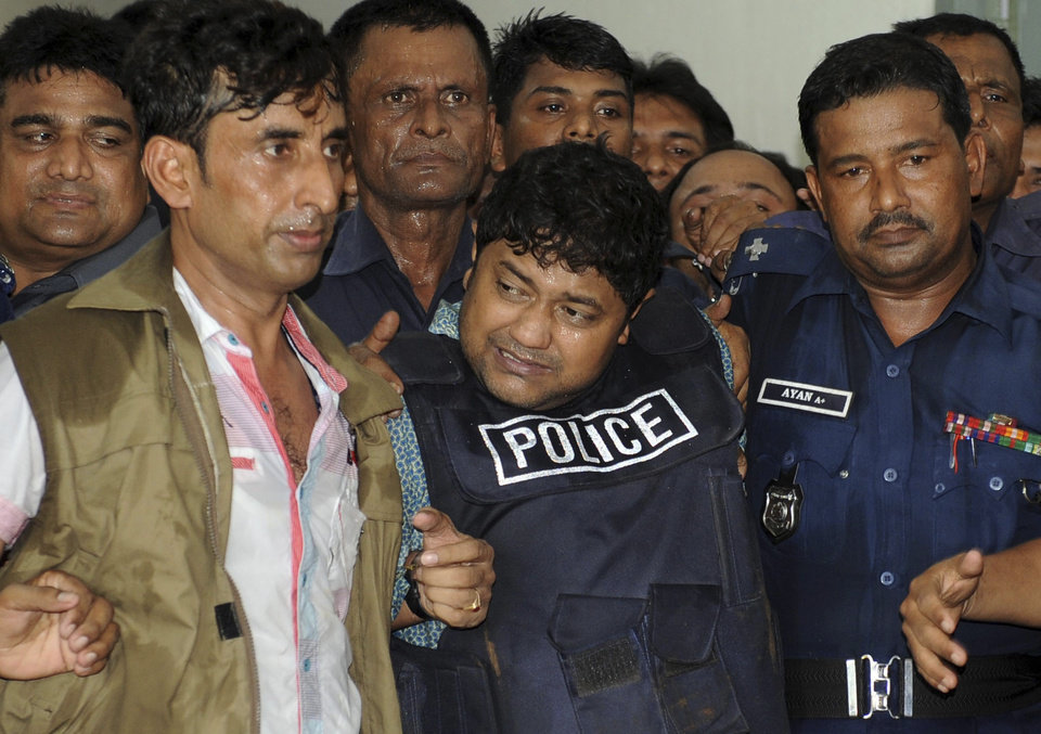 Photo - Mohammed Sohel Rana, center, the owner of a building that collapsed last week, killing at least 382 people, is brought to be produced at a court in Dhaka, Bangladesh, Monday, April 29, 2013. A Bangladesh court on Monday gave police 15 days to interrogate Rana, as rescuers used heavy machinery to cut through the destroyed structure after giving up hopes of finding any more survivors. (AP Photo)