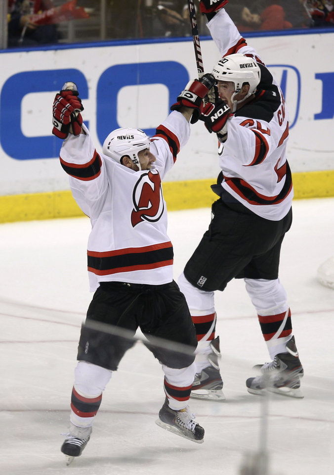 Photo -   New Jersey Devils' Stephen Gionta, left,and Ryan Carter (20) celebrate after Gionta scored a goal against the Florida Panthers during the second period of Game 7 in a first-round NHL Stanley Cup playoff hockey series, in Sunrise, Fla., Wednesday, April 26, 2012. (AP Photo/J Pat Carter)