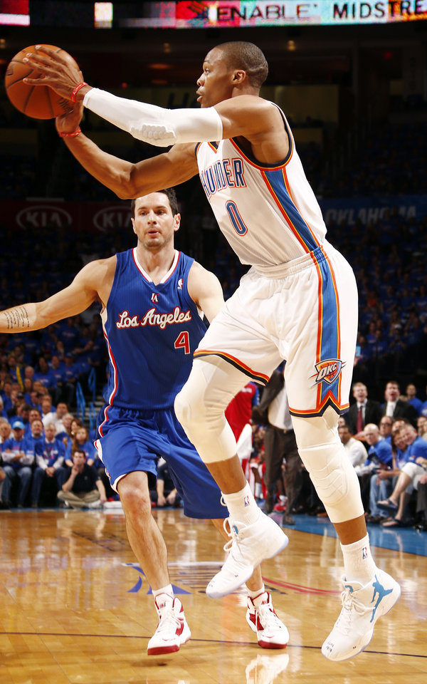 Photo - Oklahoma City's Russell Westbrook (0) passes away from Los Angeles' J.J. Redick (4) during Game 1 of the Western Conference semifinals in the NBA playoffs between the Oklahoma City Thunder and the Los Angeles Clippers at Chesapeake Energy Arena in Oklahoma City, Monday, May 5, 2014. Photo by Sarah Phipps, The Oklahoman