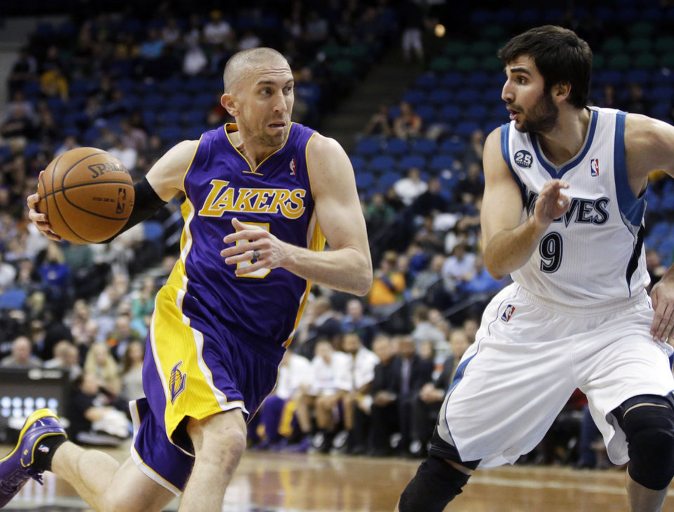Photo - Los Angeles Lakers' Steve Blake, left, drives on Minnesota Timberwolves' Ricky Rubio, of Spain, during the second half of an NBA basketball game, Tuesday, Feb. 4, 2014, in Minneapolis. The Timberwolves won 109-99. (AP Photo/Jim Mone)