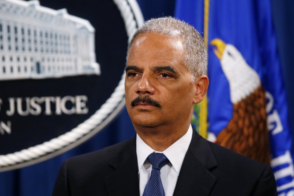 Photo - Attorney General Eric Holder listens during a news conference at the Justice Department in Washington, Monday, May 19, 2014. Holder announced that a U.S. grand jury has charged five Chinese hackers with economic espionage and trade secret theft, the first-of-its-kind criminal charges against Chinese military officials in an international cyber-espionage case. (AP Photo/Charles Dharapak)
