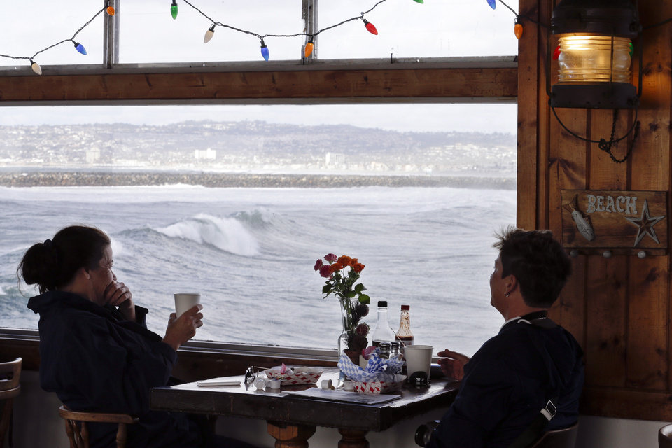 Photo - Cheryl McIntyre, left, and  Danielle Higman, right, both of San Diego, watch large waves roll under the Ocean Beach pier from the Walking on Water Cafe on the pier Friday, Dec. 11, 2015, in San Diego. Large waves lashed much of the Southern California coastline Friday, prompting the National Weather Service to issue a high surf warning through the weekend. (AP Photo/Gregory Bull)