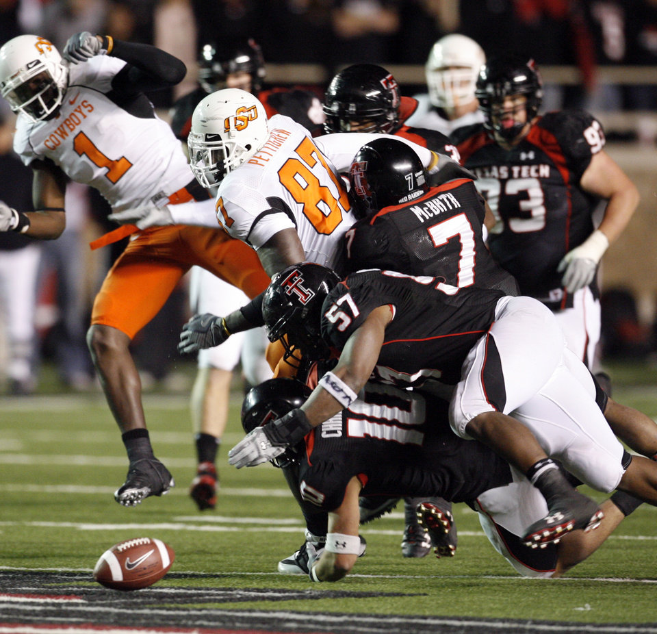 Photo - Brandon Pettigrew fumbles after a catch during the second half of the college football game between the Oklahoma State University Cowboys (OSU) and the Texas Tech Red Raiders at Jones AT&T Stadium on Saturday, Nov. 8, 2008, in Lubbock, Tex.  Texas tech won 56-20.By Steve Sisney/The Oklahoman
