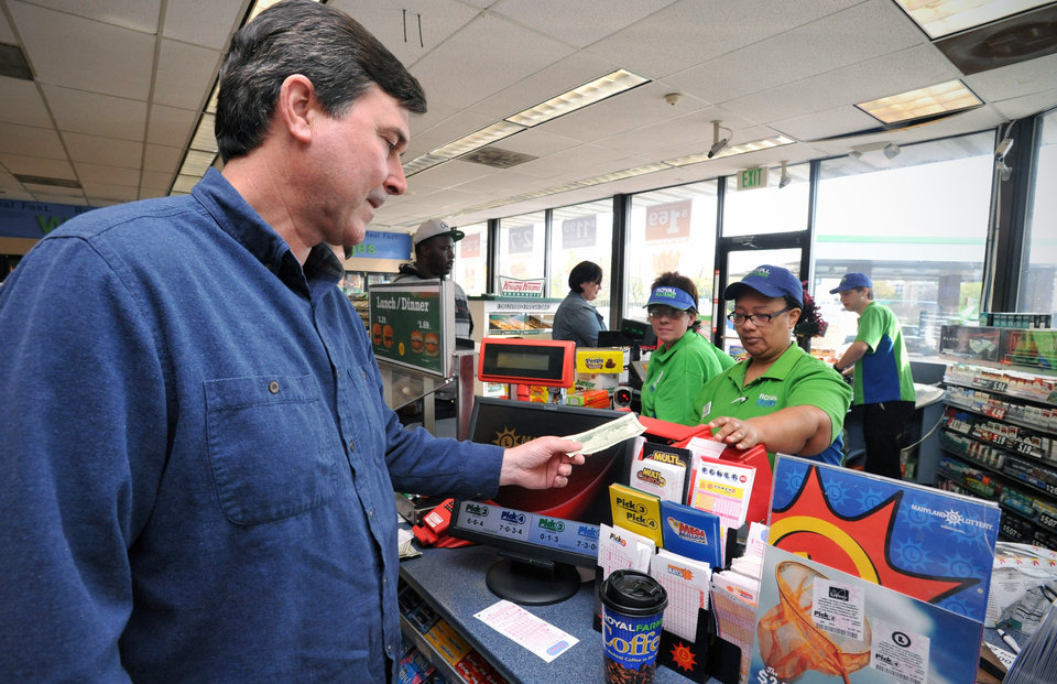 Dennis Higgins of Seaford, Del., left, buys a Mega Millions lottery ticket at the Royal Farms on N. Salisbury Blvd. in Salisbury on Friday, March 30, 2012. Lottery ticket lines across the U.S. swelled Friday as players drawn by a record $640 million Mega Millions jackpot took a chance at becoming an overnight millionaire. The jackpot odds were at 1 in 176 million. Employees Shoneek Taylor and Vicki Sharples are at right. (AP Photo/The Daily Times, Laura Emmons) NO SALES