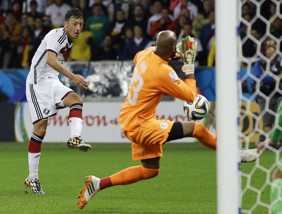 Photo - Germany's Mesut Ozil, left, kicks his team's second goal past Algeria's goalkeeper Rais M'Bolhi in extra time during the World Cup round of 16 soccer match between Germany and Algeria at the Estadio Beira-Rio in Porto Alegre, Brazil, Monday, June 30, 2014. Germany defeated Algeria 2-1 to advance to the quarterfinals. (AP Photo/Kirsty Wigglesworth)