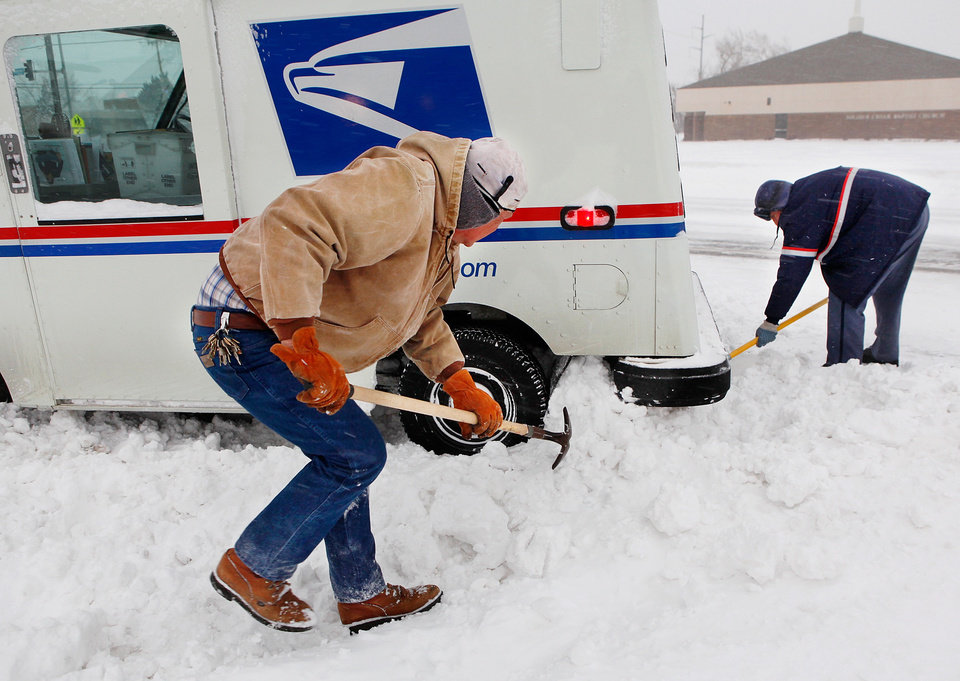 Photo - Russell Henderson noticed postal worker George Staros needed some help getting out of a snow drift on Douglas Blvd. near SE 15th Street. Henderson attached a chain from his truck to the mail truck and then helped dig snow from beneath the tires of Staros' vehicle. Within ten minutes, the two men had freed the vehicle and Staros continued with his mail delivery. A winter storm created whiteout conditions and caused snow drifts that made problems for the few motorists who ventured out Tuesday morning, Feb. 1, 2011.    Photo by Jim Beckel, The Oklahoman