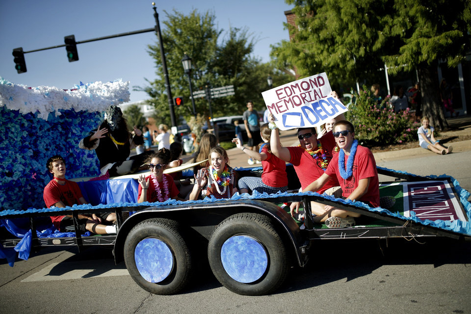 Photo - DECA club members ride in the Edmond Memorial High School homecoming parade. PHOTO BY BRYAN TERRY, THE OKLAHOMAN.  Bryan Terry - THE OKLAHOMAN