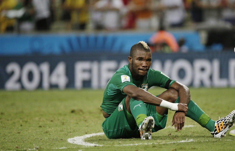 Photo - Ivory Coast's Serey Die sits on the pitch after Greece's 2-1 victory over Ivory Coast during the group C World Cup soccer match between Greece and Ivory Coast at the Arena Castelao in Fortaleza, Brazil, Tuesday, June 24, 2014. (AP Photo/Christophe Ena)