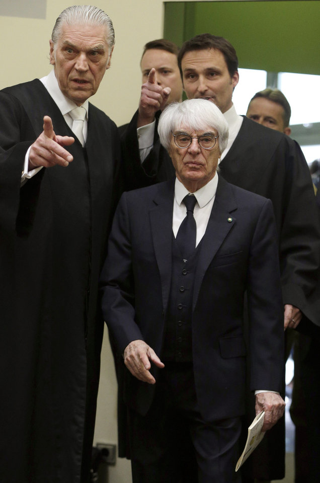 Photo - Formula One boss Bernie Ecclestone, right, arrives in the regional court in in Munich, Germany, Thursday, April 24, 2014. Ecclestone is charged with bribery and incitement to breach of trust