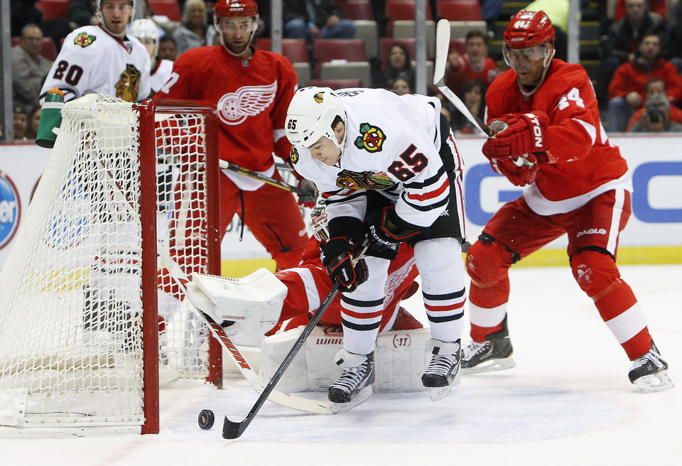 Photo - Chicago Blackhawks center Andrew Shaw (65) scores a goal against Detroit Red Wings goalie Jonas Gustavsson, of Sweden, in the first period of an NHL hockey game Wednesday, Jan. 22, 2014, in Detroit. (AP Photo/Paul Sancya)