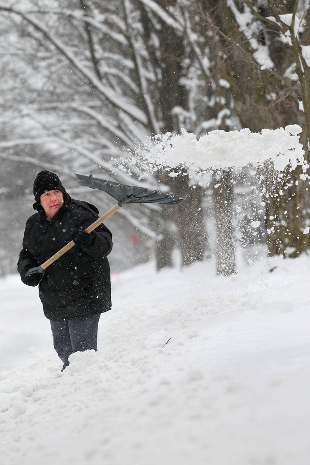 Photo - Katherine Sleder shovels her driveway outside her home, Friday, Jan. 25, 2013, in Traverse City, Mich.