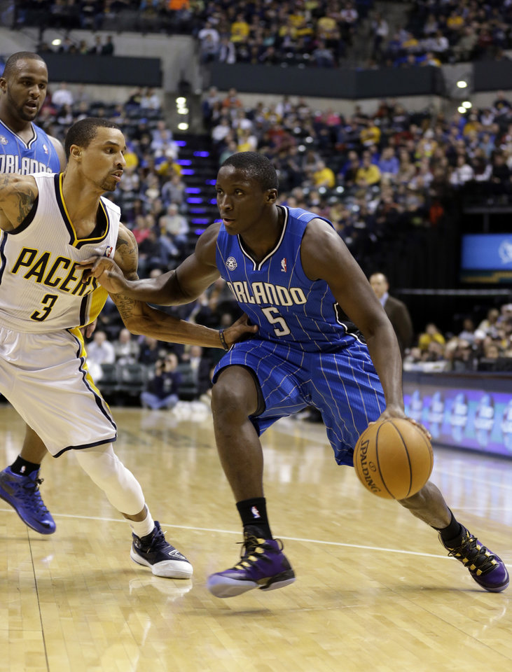 Photo - Orlando Magic guard Victor Oladipo, right, drives on Indiana Pacers guard George Hill in the first half of an NBA basketball game in Indianapolis, Monday, Feb. 3, 2014. (AP Photo/Michael Conroy)