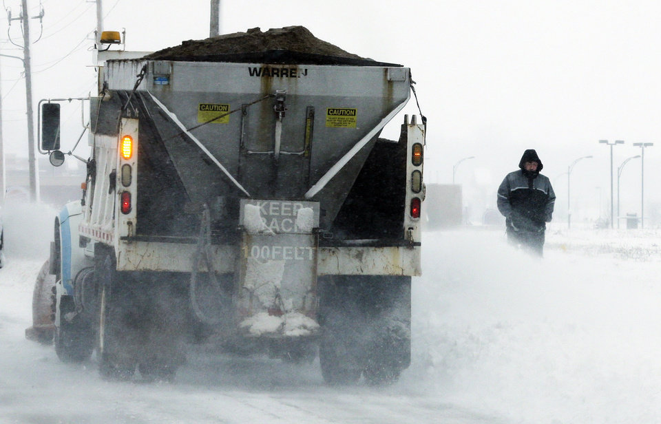 Photo - A plow spreads salt and clears snow near a pedestrian in Lawrence, Kan., Sunday, March 24, 2013. Few signs of spring are being found in parts of the Midwest as a snowstorm brings heavy snow and high winds. (AP Photo/Orlin Wagner)