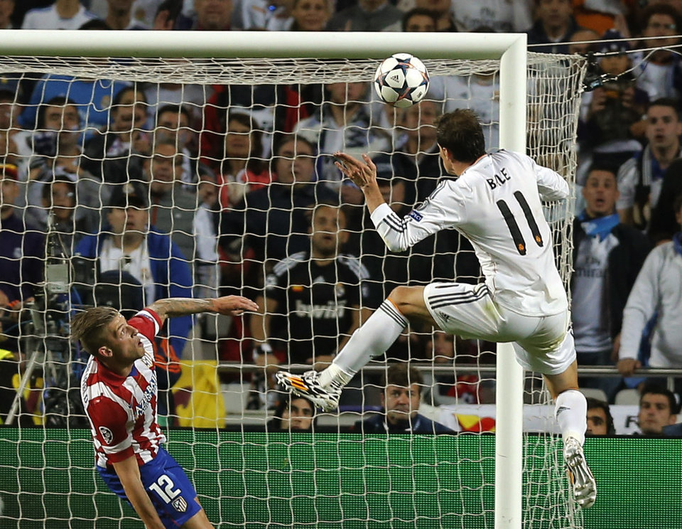 Photo - Real's Gareth Bale, right,  scores his side's 2nd goal, during the Champions League final soccer match between Atletico de Madrid and Real Madrid, at the Luz stadium, in Lisbon, Portugal, Saturday, May 24, 2014. (AP Photo/Daniel Ochoa de Olza)