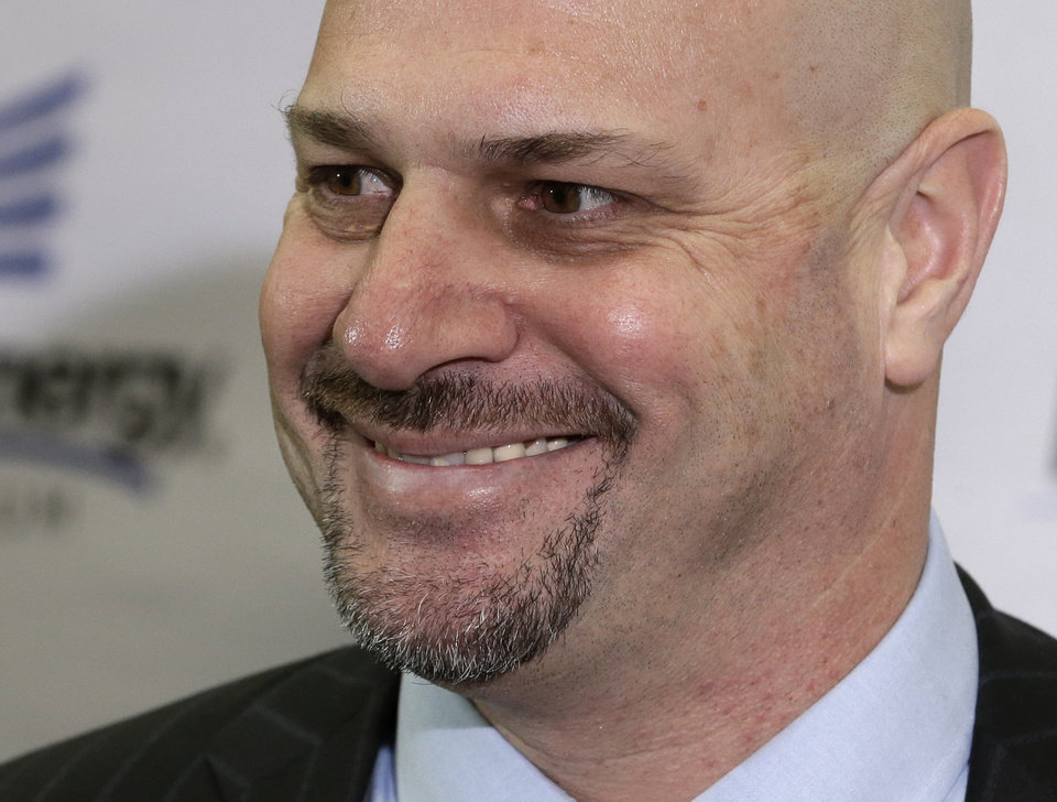 Photo - Cleveland Browns coach Mike Pettine smiles as he answers questions Thursday, Jan. 23, 2014, in Berea, Ohio. The 47-year-old Pettine, the son of a legendary Pennsylvania high school coach, spent one year with the Buffalo Bills after four as Rex Ryan's defensive coordinator with the New York Jets. (AP Photo/Tony Dejak)