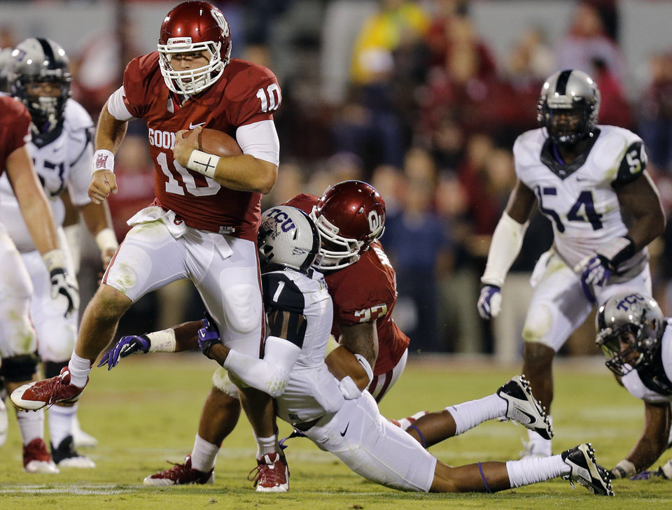 Photo - Oklahoma's Blake Bell (10) runs past TCU 's Chris Hackett (1) during the college football game between the University of Oklahoma Sooners (OU) and the Texas Christian University Horned Frogs (TCU) at the Gaylord Family-Oklahoma Memorial Stadium on Saturday, Oct. 5, 2013 in Norman, Okla.   Photo by Chris Landsberger, The Oklahoman