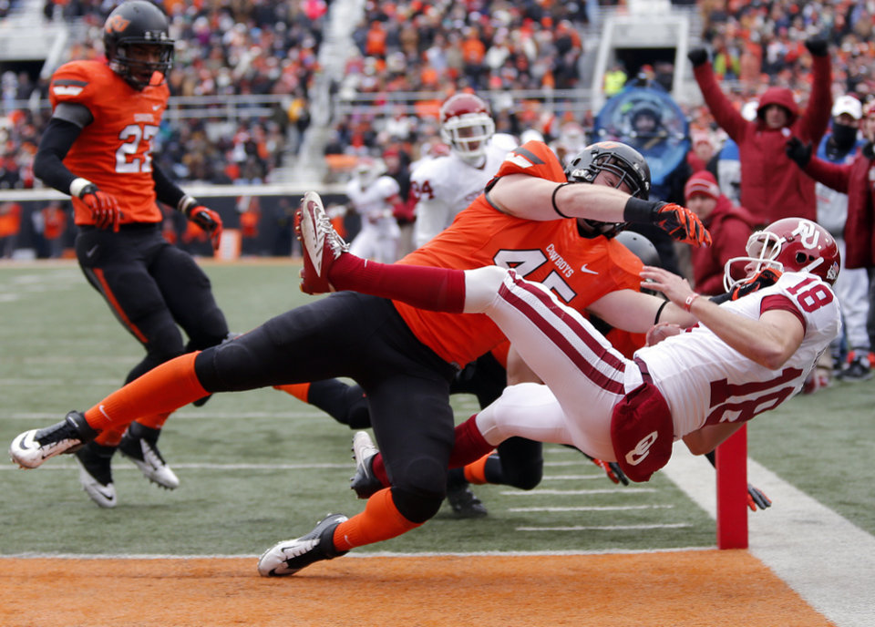 Oklahoma's Michael Hunnicutt (18) scores a touchdown as he is hit by Oklahoma State's Caleb Lavey (45) on a fake field goal attempt during the Bedlam college football game between the Oklahoma State University Cowboys (OSU) and the University of Oklahoma Sooners (OU) at Boone Pickens Stadium in Stillwater, Okla., Saturday, Dec. 7, 2013. Photo by Chris Landsberger, The Oklahoman