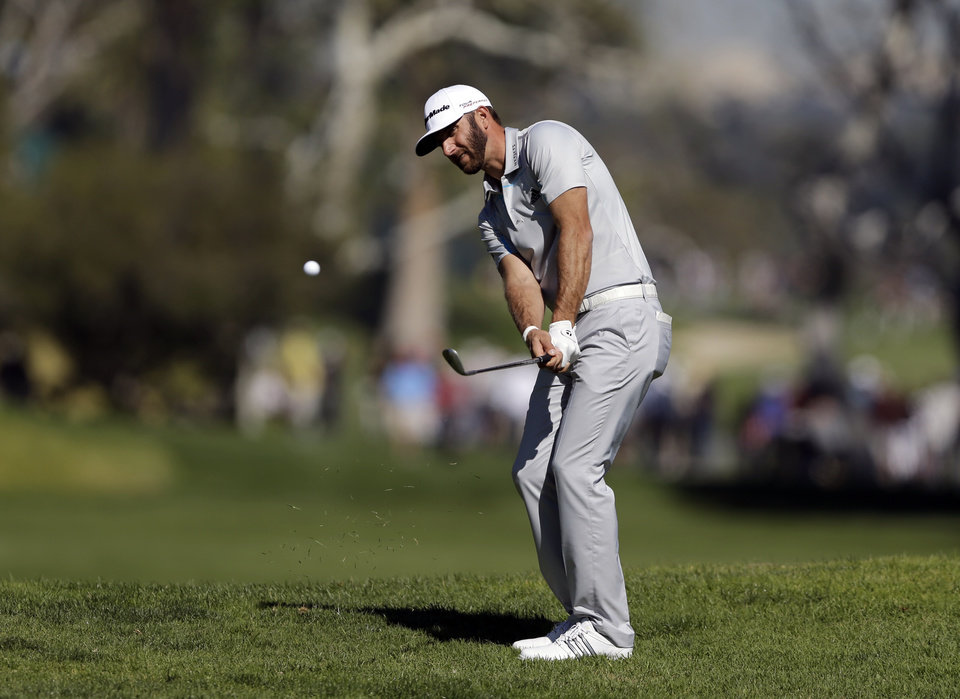 Photo - Dustin Johnson chips to the fourth green in the second round of the Northern Trust Open golf tournament at Riviera Country Club in the Pacific Palisades area of Los Angeles, Friday, Feb. 14, 2014. (AP Photo/Reed Saxon)
