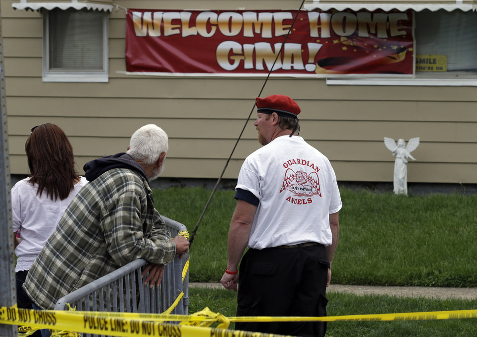 Photo - A member of the Guardian Angels stands watch outside the home of Gina DeJesus in Cleveland Friday, May 10, 2013. DeJesus was freed Monday from the home of Ariel Castro where she and two other women had been held captive for nearly a decade. (AP Photo/Mark Duncan)