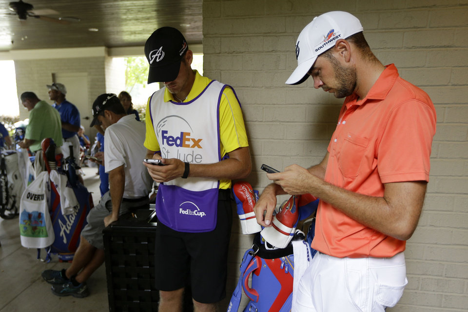 Photo - Golfer Troy Merritt, right, checks his phone during a weather delay during the first round of the St. Jude Classic golf tournament Thursday, June 5, 2014, in Memphis, Tenn. (AP Photo/Mark Humphrey)