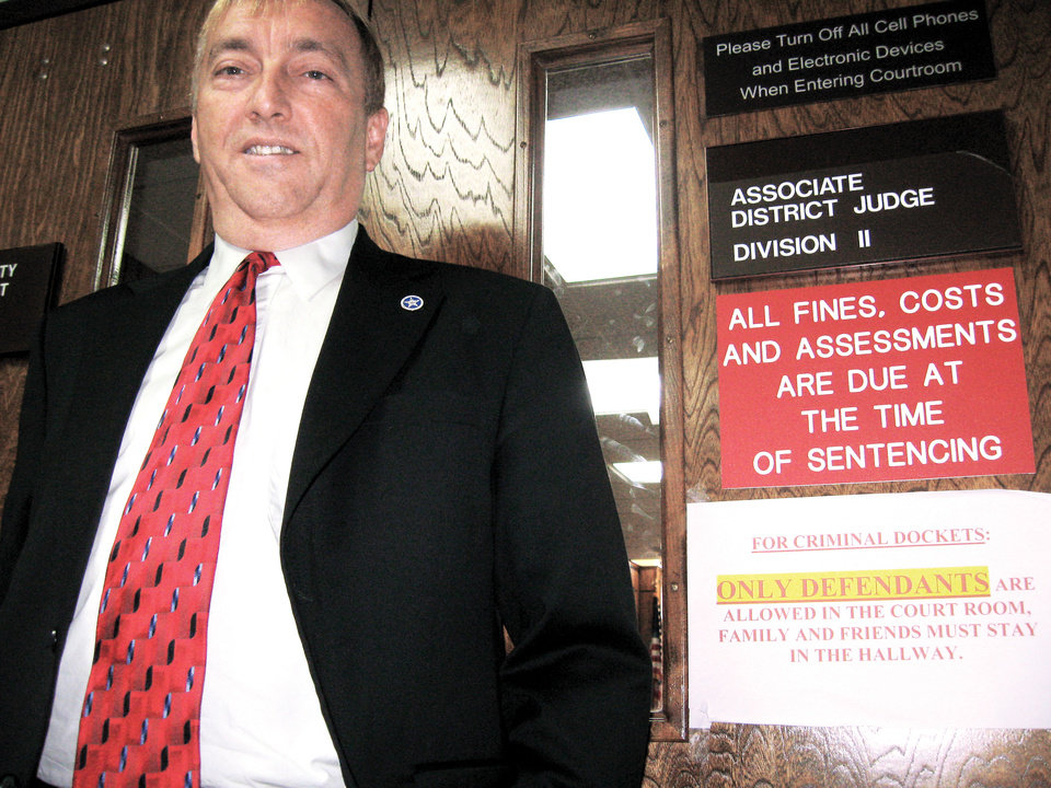 Photo - David Starkey stands next to a sign on the door to District Judge Dwayne Steidley's courtroom in Rogers County that tells people the public isn't welcome. By Tony Thornton
