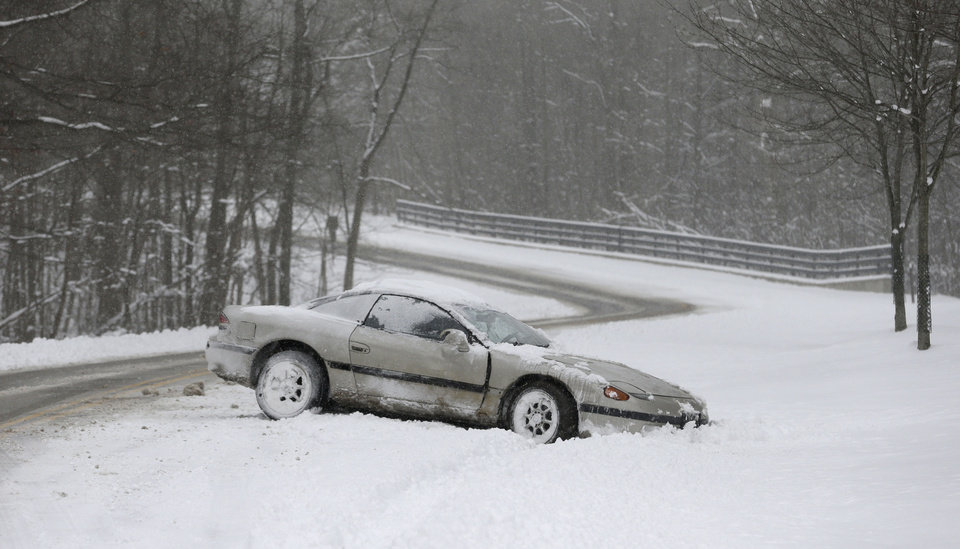 A car rests on the side of the road in the snow Friday, Feb. 1, 2013, in Solon, Ohio. Temperatures in northeast Ohio will remain in the teens Friday with a possibility of  three to five inches of new snow in areas. (AP Photo/Tony Dejak)