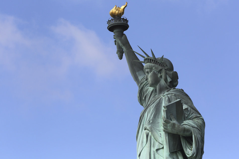 The Statue of Liberty stands against a clear sky Thursday, July 4, 2013, on the first day it opened to tourists since Superstorm Sandy swamped its little island in New York Harbor. The statue was spared in the fall storm, but most of the national landmark's 12-acre island took a serious beating. (AP Photo/Mary Altaffer)