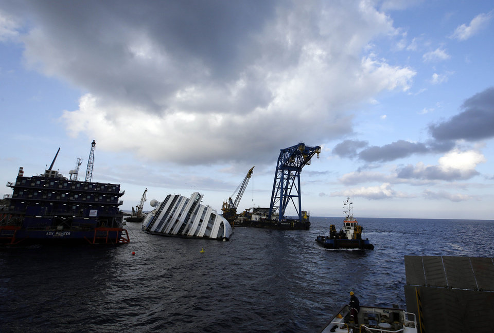 The Costa Concordia cruise ship leans on its side of the Tuscan Island Isola del Giglio, Italy, Saturday, Jan. 12, 2013. More time and money will be needed to remove the Costa Concordia cruise ship from the rocks off Tuscany where it capsized last year, in part to ensure the toxic materials still trapped inside don't leak into the marine sanctuary when it is righted, officials said Saturday. On the eve of the first anniversary of the grounding, environmental and salvage experts gave an update on the unprecedented removal project under way, stressing the massive size of the ship � 112,000 tons, its precarious perch on the rocks off the port of Giglio island and the environmental concerns at play. (AP Photo/Gregorio Borgia)