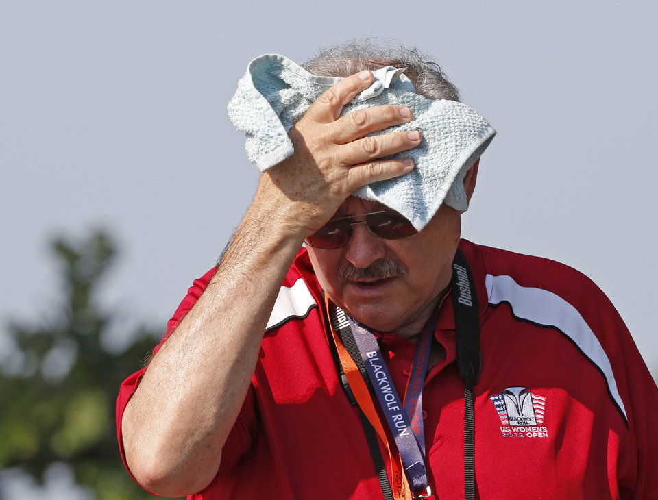 A volunteer wipes his head while walking around the course during the second round of the U.S. Women's Open golf tournament, Friday, July 6, 2012, in Kohler, Wis. (AP Photo/Jeffrey Phelps)