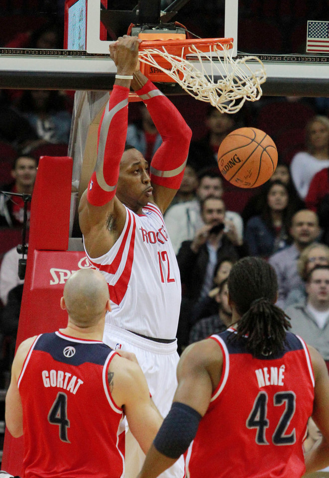 Photo - Houston Rockets center Dwight Howard, top, scores as Washington Wizards center Martin Gortat (4) and forward Nene (42) watch during the first half of an NBA basketball game in Houston, Wednesday, Feb. 12, 2014. (AP Photo/Richard Carson)