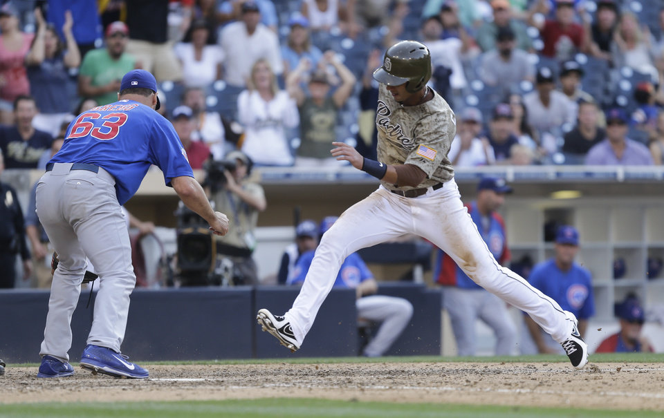 Photo - San Diego Padres' Ronny Cedeno scores as Chicago Cubs relief pitcher Kevin Gregg searches for the ball in the thirteenth inning of a baseball game Sunday, Aug. 25, 2013, in San Diego. Cedeno scored from third on a wild pitch.  (AP Photo/Lenny Ignelzi)