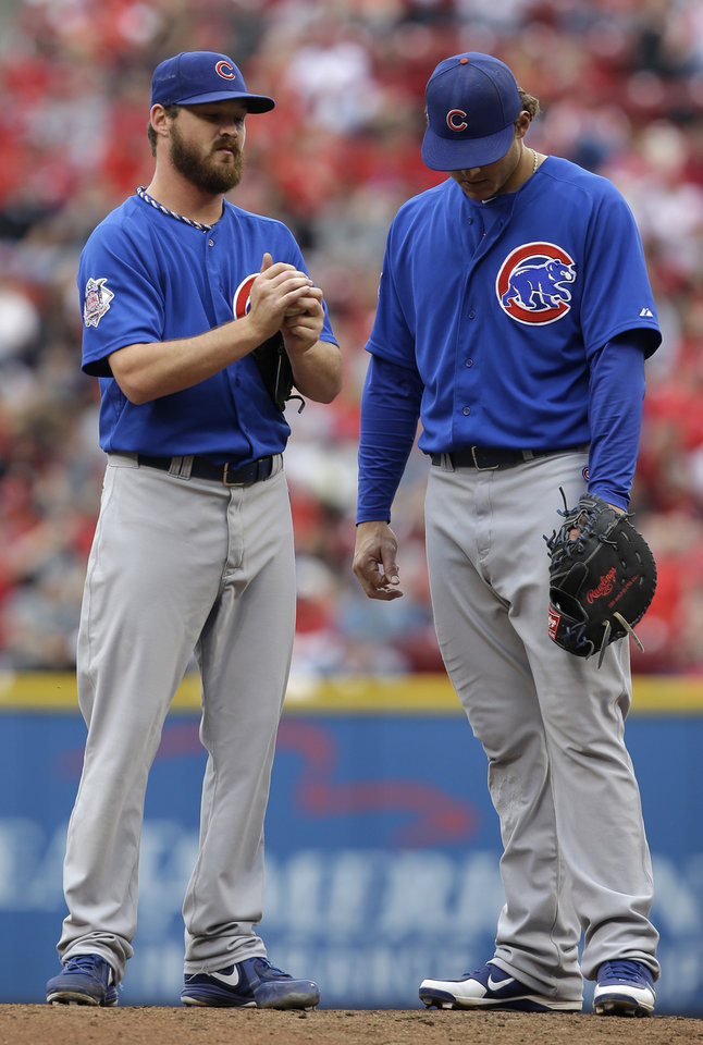 Photo - Chicago Cubs starting pitcher Travis Wood, left, stands with first baseman Anthony Rizzo on the mound in the fourth inning of a baseball game against the Cincinnati Reds, Saturday, May 25, 2013, in Cincinnati. (AP Photo/Al Behrman)