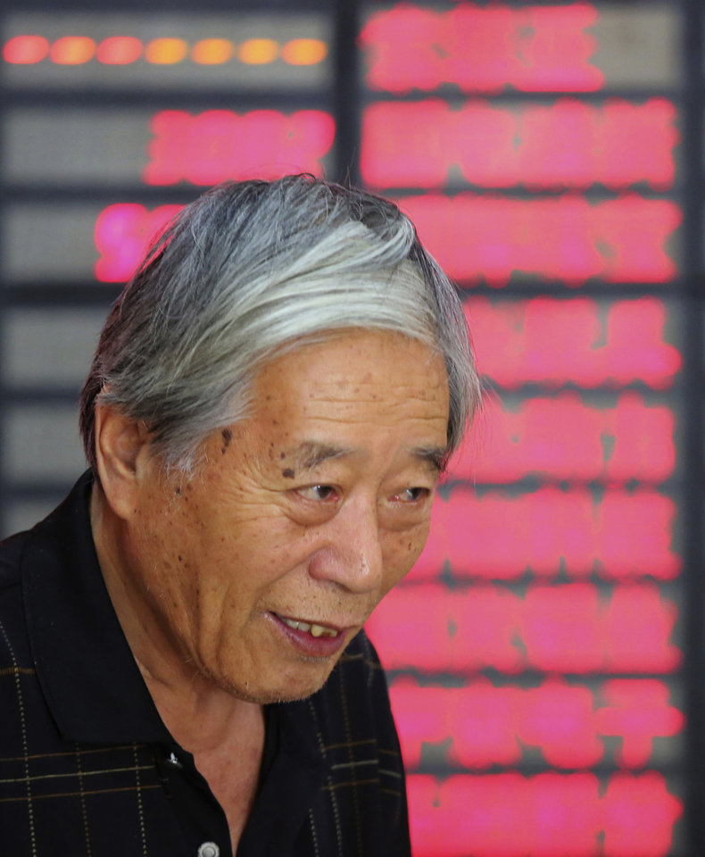 Photo - An investor stands in front of the stock price monitor at a private securities company on Monday July 15, 2013 in Shanghai, China. Asian stock markets posted modest gains Monday, registering relief that a slowdown in China's economic growth wasn't as sharp as feared. (AP Photo)