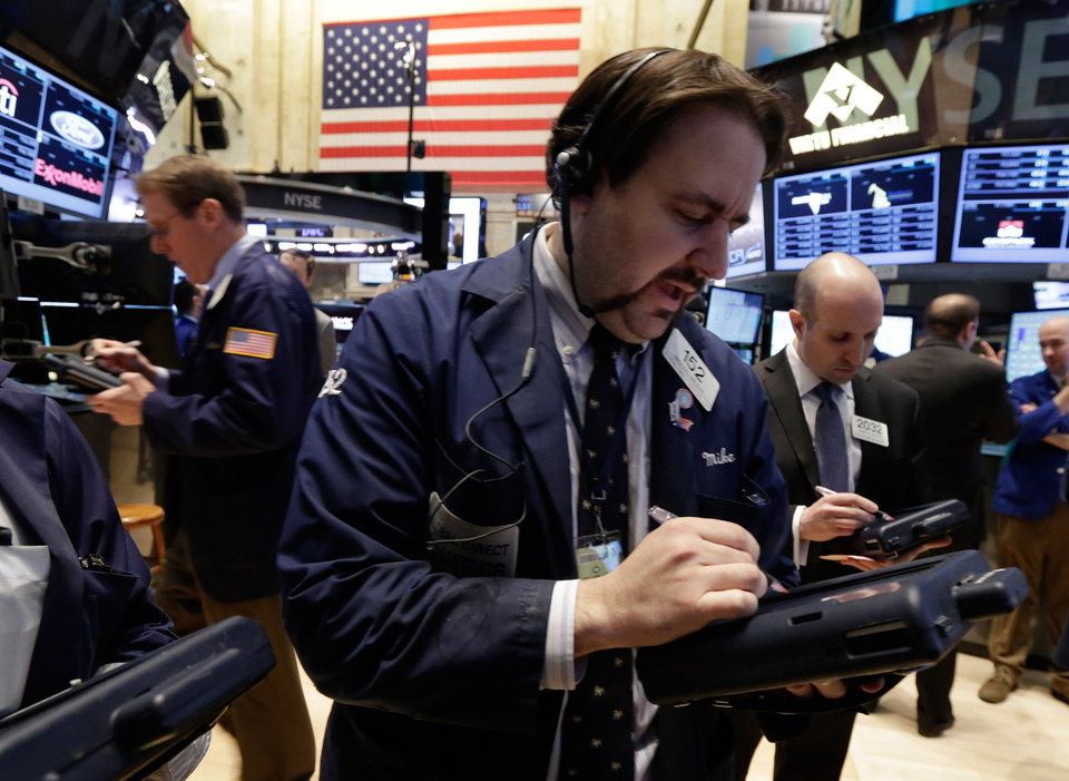 Photo - Trader Michael Mozian works on the floor of the New York Stock Exchange, Wednesday, March 5, 2014. Stocks are little changed in early trading, a day after setting a record high, as traders were unimpressed by a slight increase in hiring at private companies last month.(AP Photo/Richard Drew)