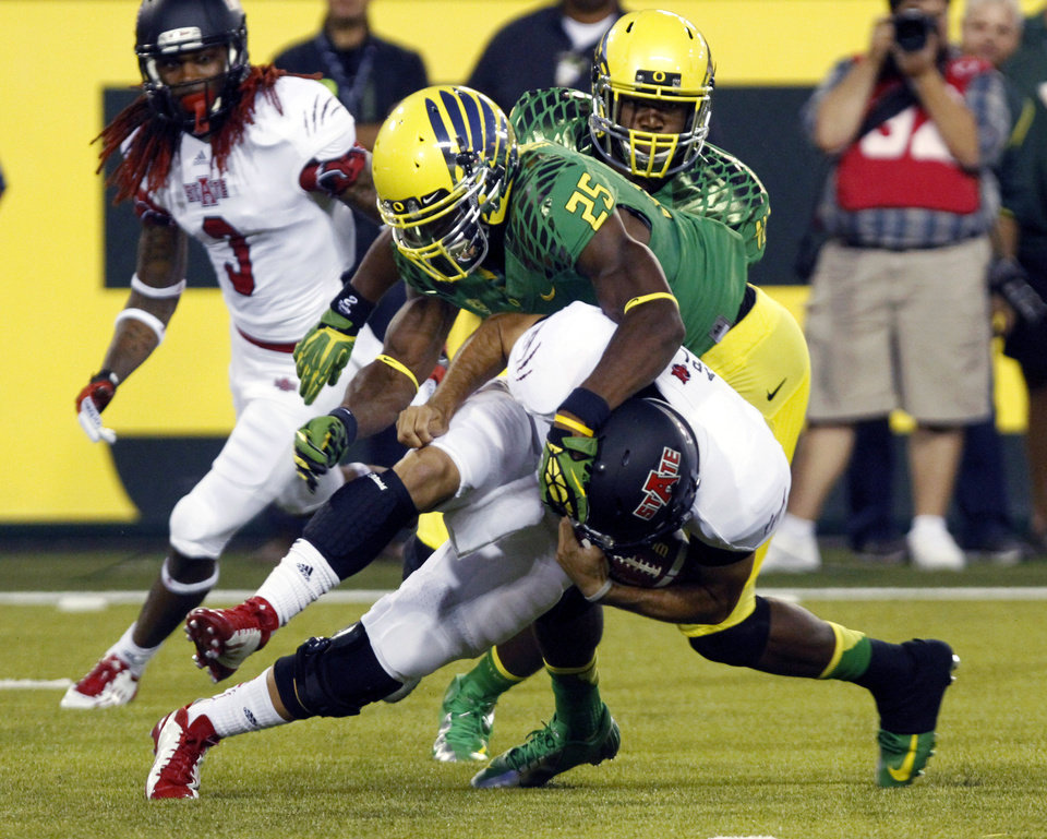Photo -   Arkansas State quarterback Ryan Aplin, bottom, is wrapped up by Oregon defender Boseko Lokombo during the first half of their college football game in Eugene, Ore., Saturday, Sept. 1, 2012. (AP Photo/Don Ryan)