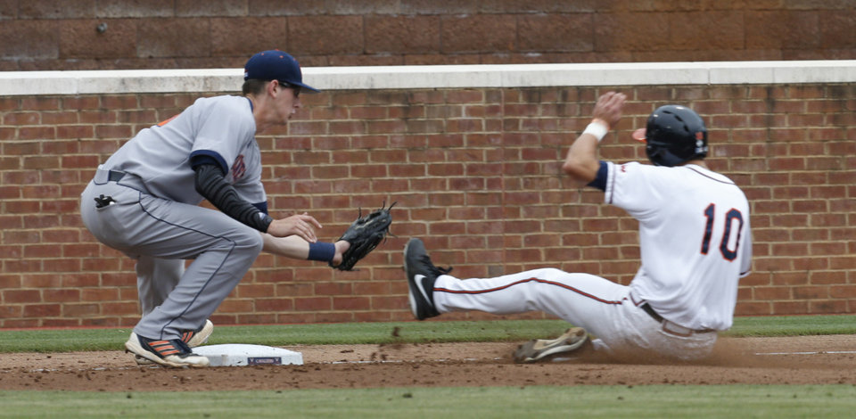 Photo - Bucknell third baseman Sam Clark (26) waits to tag Virginia outfielder Brandon Downes (10) out at third base during an NCAA College regional tournament baseball game in Charlottesville, Va., Friday, May 30, 2014.   (AP Photo/Steve Helber)