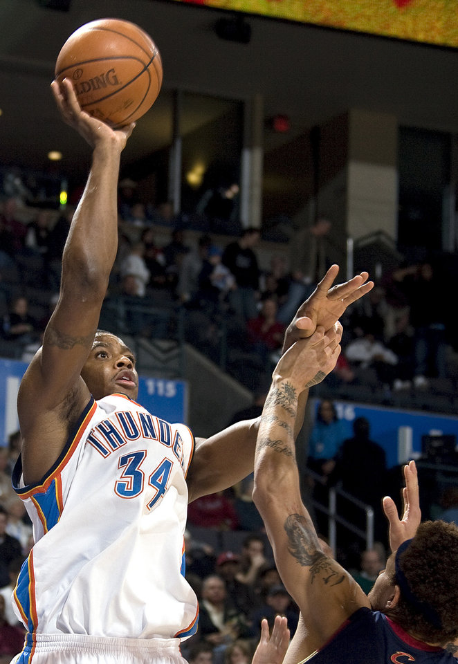 Photo - Oklahoma City's Desmond Mason  (34) shoots over Cleveland's Delonte West (13) during the NBA game between the Oklahoma City Thunder and Cleveland Cavaliers, Sunday, Dec. 21, 2008, at the Ford Center in Oklahoma City. PHOTO BY SARAH PHIPPS, THE OKLAHOMAN
