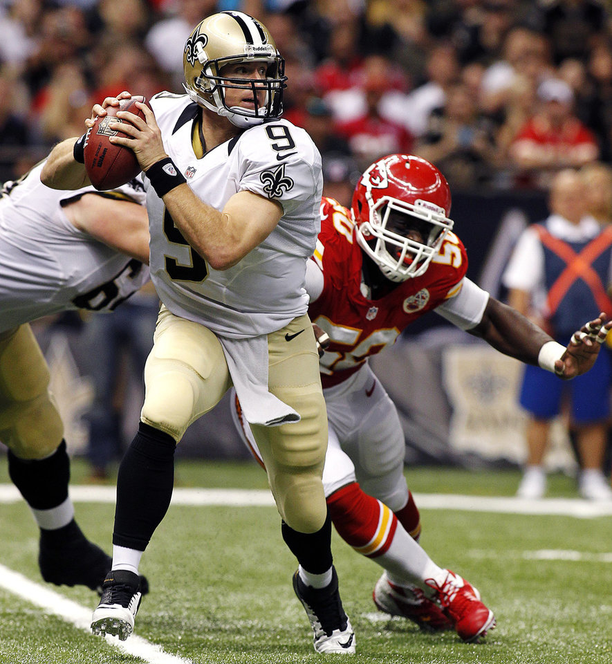 New Orleans Saints quarterback Drew Brees (9) scrambles from Kansas City Chiefs outside linebacker Justin Houston (50) in the second half of an NFL football game in New Orleans, Sunday, Sept. 23, 2012. (AP Photo/Jonathan Bachman)