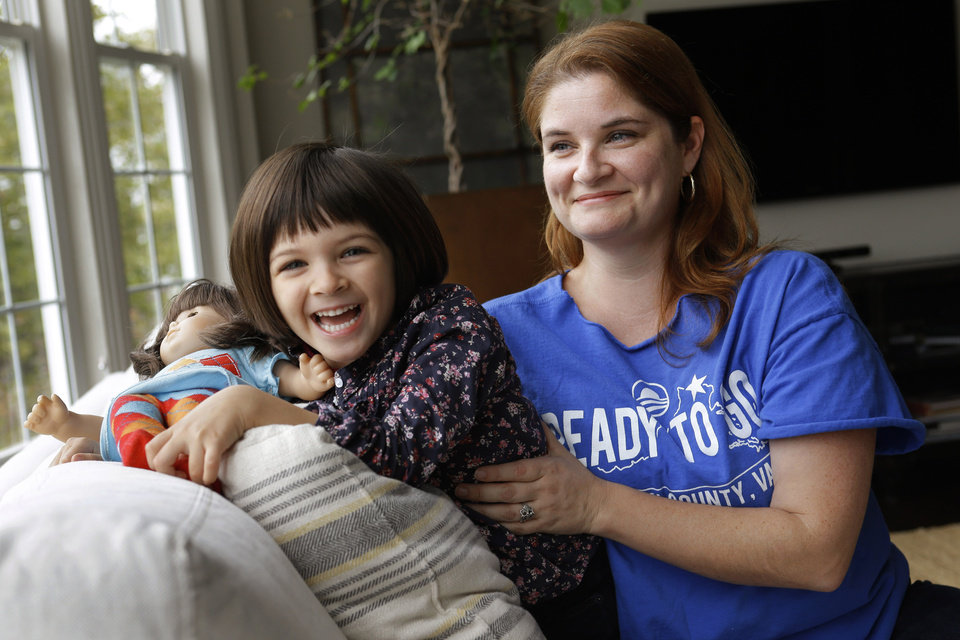 Photo -   In this Monday, Oct. 8, 2012 photo, Molly Lovato, a volunteer with the Obama campaign, poses for a photograph with her daughter Nola Trindade, 4, at their home in Leesburg, Va. Lovato credits the president with steering the country away from financial disaster.