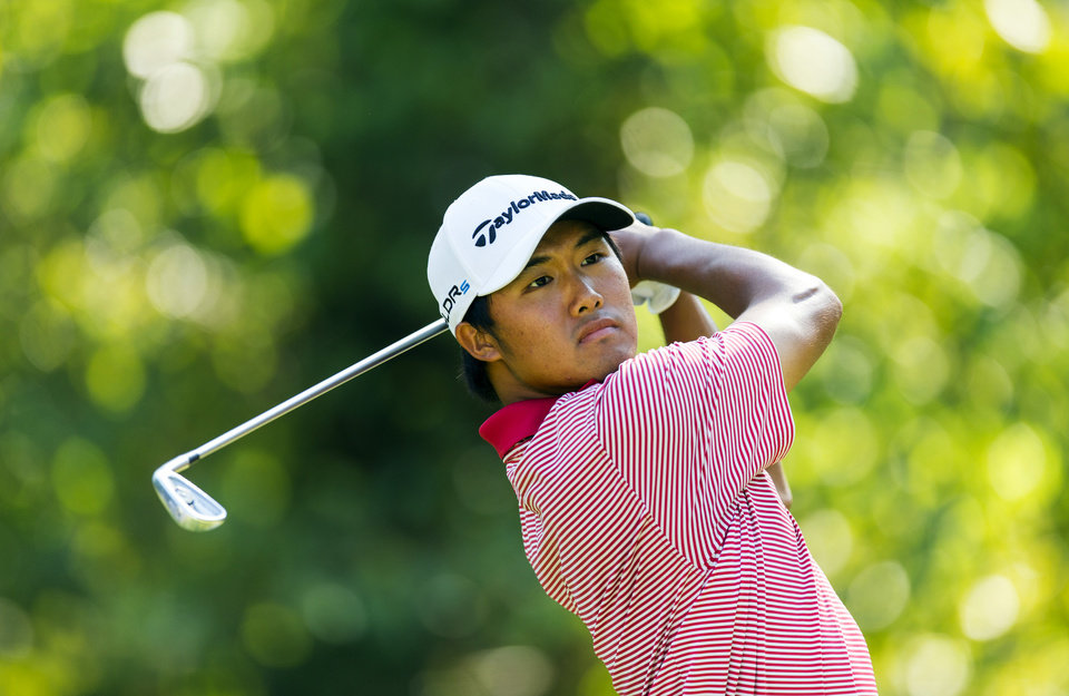 Photo - In this photo released by the USGA, Gunn Yang, of South Korea, watches his tee shot on the 13th hole during the semifinal round of match play at the U.S. Amateur Championship golf tournament at Atlanta Athletic Club in Johns Creek, Ga., Saturday, Aug. 16, 2014.  (AP Photo/USGA, Chris Keane)