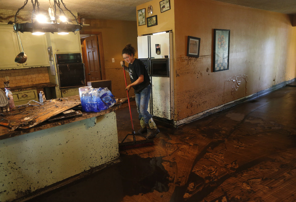 Photo - Jerni Self sweeps mud out of the kitchen of the Easter home after the West Cache Creek overflowed and flooded the area, Sunday, May 24, 2015, in Cache, Okla., Photo by Sarah Phipps, The Oklahoman