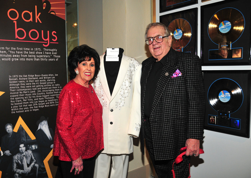 Photo - Oklahoma music pioneer Wanda Jackson, left, and impresario Jim Halsey pose with Oak Ridge Boy Duane Allen's Manuel Cuevas-designed suit at the January opening event for the exhibit